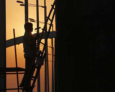 A labourer works on a flyover beside the Jawaharlal Nehru Stadium in New Delhi