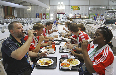 Members of the England Commonwealth Games team enjoy a meal at the food court in the Games Village