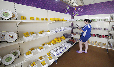 A member of the Scottish team browses through artifacts inside a handicraft shop at the Games Village