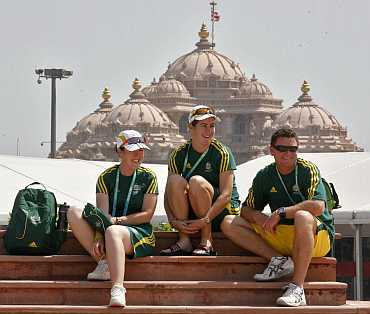 Australian athletes sit in front of the 'Akshardham temple at the Commonwealth Games athletes village