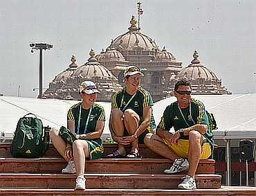 Australian athletes sit in front of the Akshardham temple at the Commonwealth Games athletes village