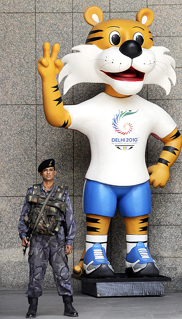 A security personnel stands guard besides the mascot of the 2010 Com