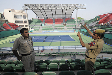 Indian policemen chat inside the RK Khanna Tennis stadium in New Delhi