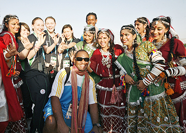 New Zealand athletes pose with Indian performers on their arrival in the Games Village