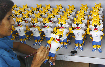 An artisan paints a model of the mascot of the Commonwealth Games inside a factory in Mohali