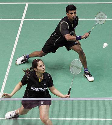 V Diju and Jwala Gutta play a return shot during their mixed doubles match at the 2010 Badminton World Championships in Paris