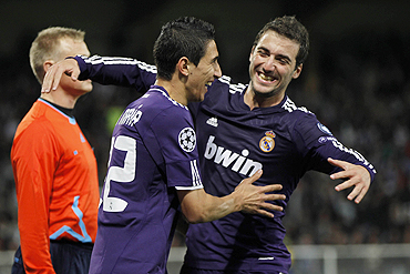 Real Madrid's Angel Di Maria celebrates with teammate Higuain after scoring against Auxerre