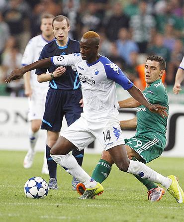 Dame N'Doye of FC Copenhagen (front) dribbles past Panathinaikos FC defender Kostas Katsouranis