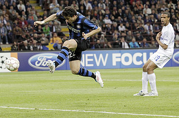 Inter Milan's Diego Milito (left) shoots and scores as Joel Matip of Schalke looks on
