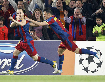 Barcelona's Andres Iniesta (left) celebrates with team-mate David Villa after scoring against Shakhtar Donetsk