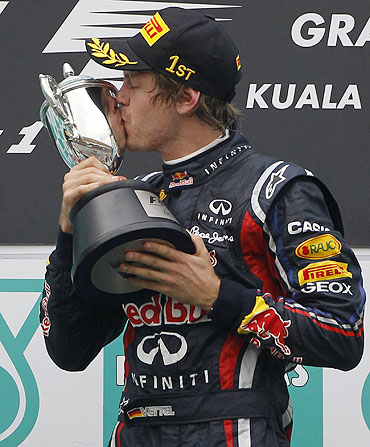 Red Bull's Sebastian Vettel kisses the winner's trophy after the Malaysian GP
