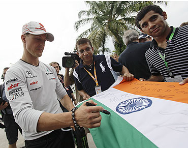 Mercedes's Michael Schumacher signs autographs on an Indian flag in the paddock
