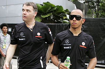McLaren's Lewis Hamilton (right) leaves the paddock after the Malaysian Grand Prix