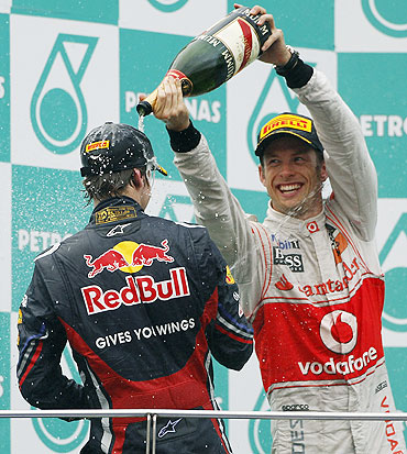 McLaren's Jenson Button (right) and Red Bull's Sebastian Vettel spray champagne on each other after winning the Malaysian GP on Sunday