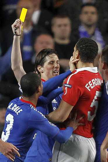 Manchester United's Ferdinand clashes with Chelsea's Torres during the first leg of their Champions League quarter final match