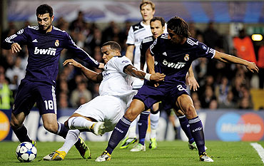 Tottenham's Tom Huddlestone is marked by Raul Albiol and Samir Khedira of Real Madrid