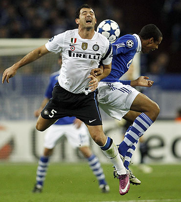 Schalke 04's Joel Matip and Inter Milan's Dejan Stankovic (left) vie for a aeriel ball
