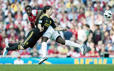 Arsenal's Johan Djourou (left) challenges Liverpool's Luis Suarez