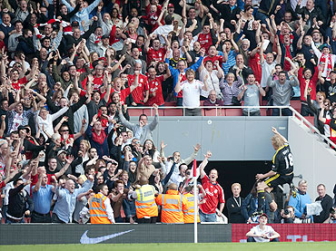Liverpool's Dirk Kuyt celebrates in front of the Liverpool fans after scoring a penalty against Arsenal