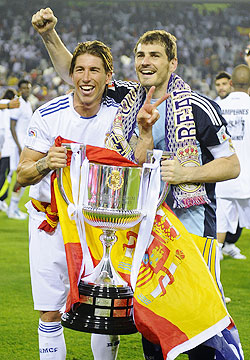 Real Madrid's captain and goalkeeper Iker Casillas (right) and teammate Sergio Ramos celebrate with the King's Cup trophy
