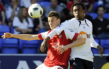 Arsenal's Laurent Koscielny (left) challenges Bolton Wanderers' Daniel Sturridge