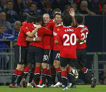Manchester United players celebrate after a goal during their Champions League semi-final first leg match against Schalke 04 in Gelsenkirchen