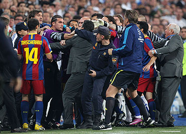 Barcelona's reserve 'keeper Jose Pinto clashes with Real Madrid official as the players leave the pitch at half time