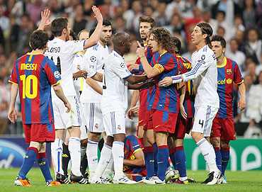 Real Madrid's Lassana Diarra and Barcelona captain Carles Puyol get into an argument mid-pitch