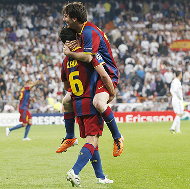 Barcelona's Lionel Messi celebrates with teammate Xavi Hernandez after scoring his second goal
