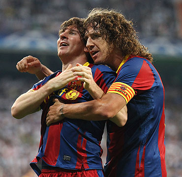 Barcelona's Lionel Messi celebrates with captain Carles Puyol