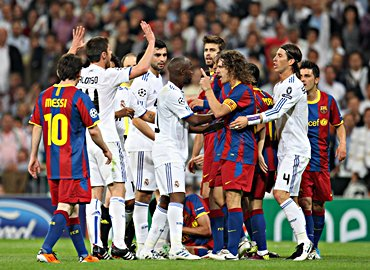 Real Madrid's Lassana Diarra and Barcelona captain Carles Puyol get into an argument during Wednesday's Champions League semi-final
