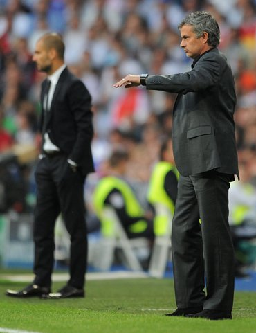 Jose Mourinho (R) stands backdropped by Barca coach Josep Guardiola