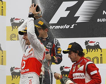 McLaren's Jenson Button (left), Red Bull's Sebastian Vettel (centre) and Ferrari's Fernando Alonso spray champagne on the podium