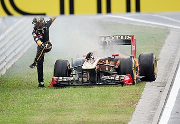 Renault's Nick Heidfeld jumps away from his burning car during the Hungarian GP at the Hungaroring circuit