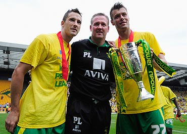 Manager of Norwich City Paul Lambert, Adam Drury and Elliot Ward celebrate the team's promotion to the EPL