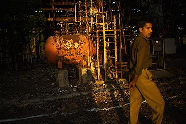 A police man looks on as he tours the site of the deserted Union Carbide factory that caused the ill-fated Bhopal Gas tragedy