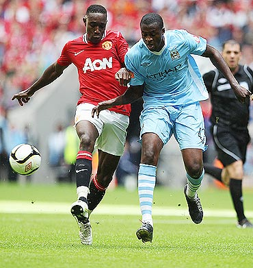 Danny Welbeck (left) and Yaya Toure of Manchester City battle for the ball during the FA Community Shield match on Sunday