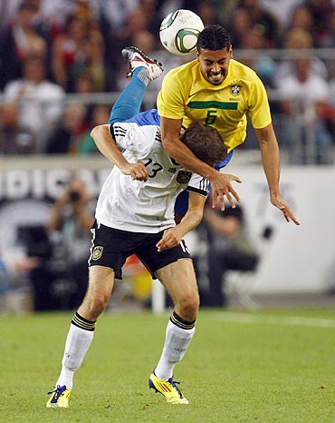 Germany's Thomas Mueller (left) and Brazil's Andre Santos get into a tangle as they vie for possession