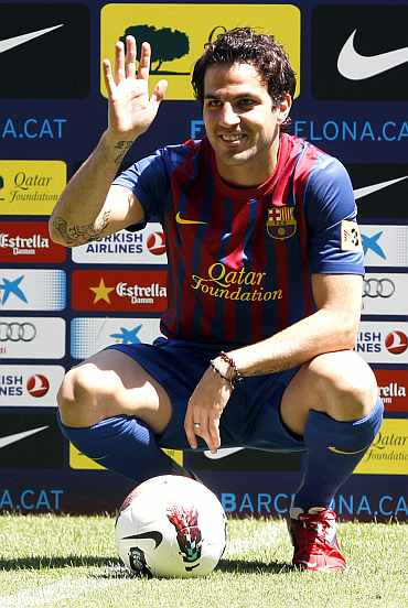 Barcelona's new player Cesc Fabregas waves to photographers during his presentation at Nou Camp stadium