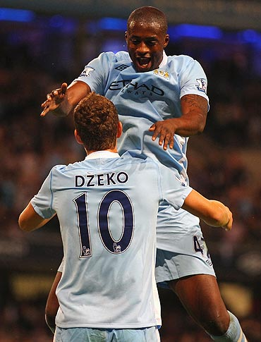 Manchester City's Edin Dzeko celebrates with teammate Yaya Toure after scoring the opening goal