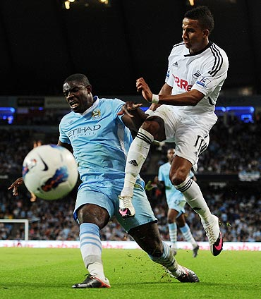 Manchester City's Micah Richards and Swansea City's Scott Sinclair vie for possession