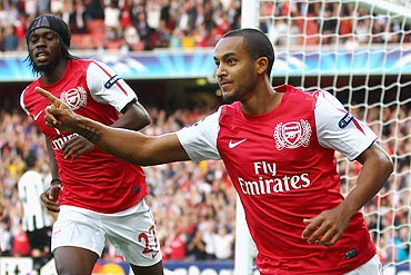 Arsenal's Theo Walcott celebrates scoring the opening goal against Udinese during their UEFA Champions League play-off first leg match