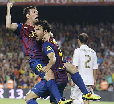 Barcelona's Lionel Messi (left) and Cesc Fabregas celebrate a goal against Real Madrid on Wednesday