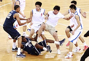 Players from American Georgetown University men's basketball team and China's Bayi men's basketball team fight during a basketball friendly game at the Beijing Olympic Basketball Arena on Thursday
