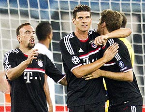 FC Bayern's Munich Mario Gomez celebrates with teammates Thomas Mueller (right) and Franck Ribery (left) after scoring against FC Zurich