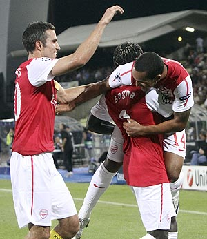 Arsenal's Theo Walcott (right) celebrates with teammates Robin van Persie (left) and Bacary Sagna (centre) after scoring against Udinese