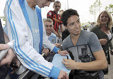 Samir Nasri signs autographs as he is greeted by fans outside Manchester City's Etihad Stadium in Manchester on Wednesday