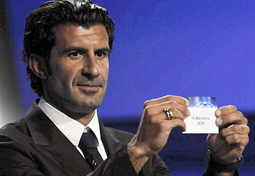 Former Portugal captan Luis Figo holds up a card showing FC Barcelona during the Champions League draw
