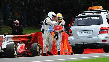 Lewis Hamilton of Great Britain and McLaren is helped into the medical car after crashing out during the Belgian Formula One Grand Prix