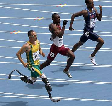Oscar Pistorius of South Africa runs to the finish line next to Femi Ogunode of Qatar and Tony McQuay of the U.S. in Daegu